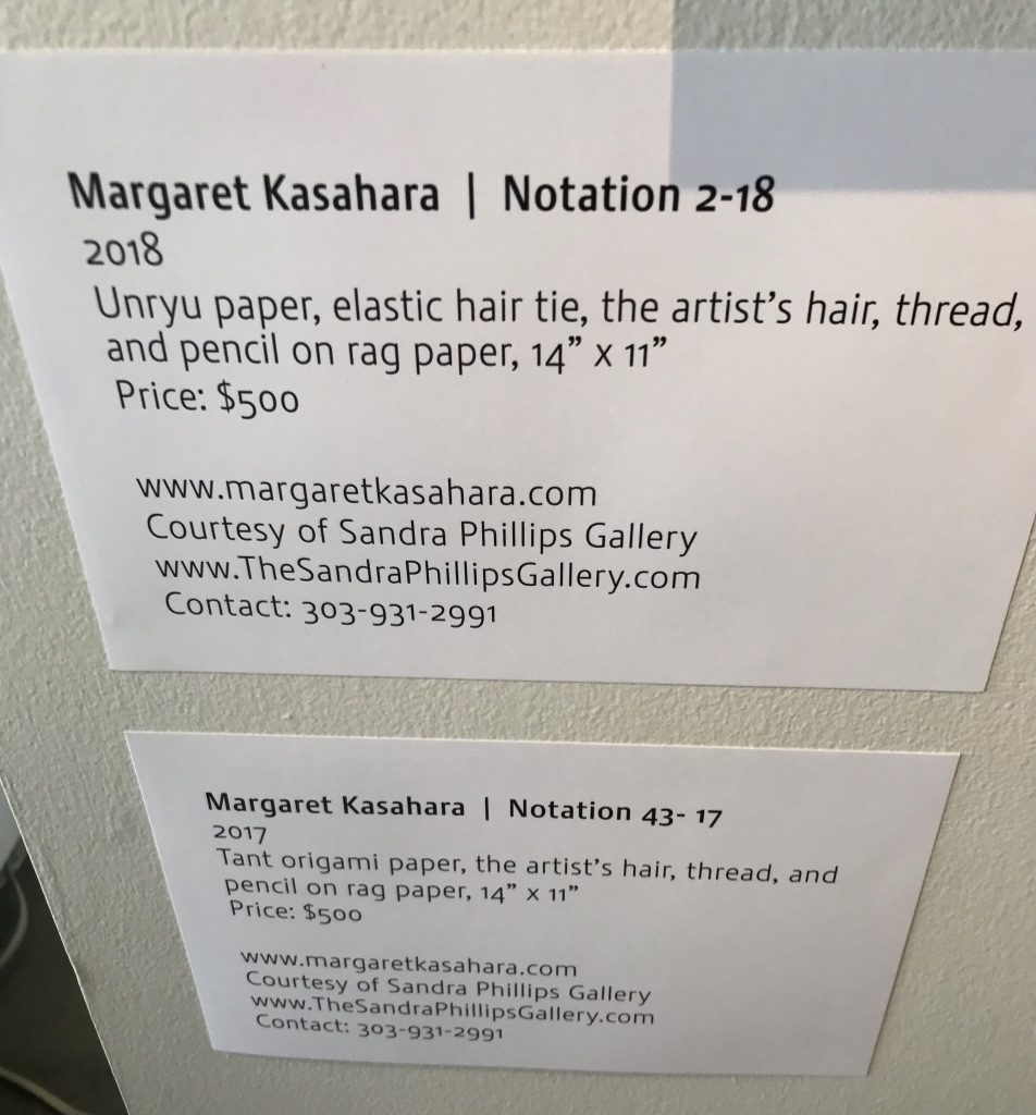 Labels next to Margaret Kasahara's artwork